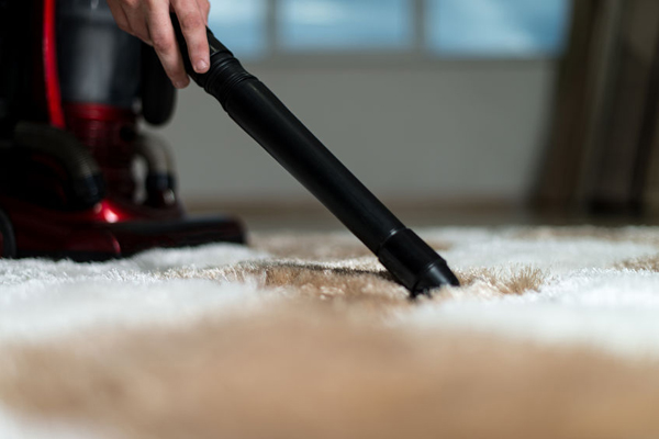 man cleaning carpet with a vacuum cleaner