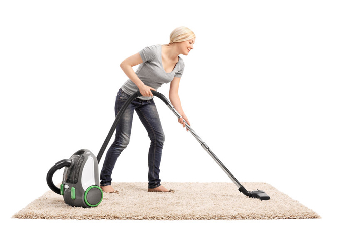woman vacuuming a beige colored carpet with a vacuum cleaner